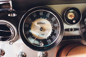 Vintage car dashboard with chrome rims speedometer tachometer.