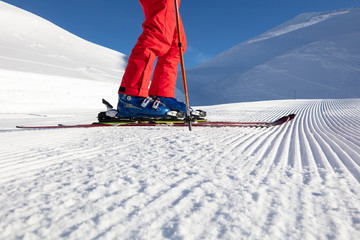 Low section of male skier with skis on a ski slope