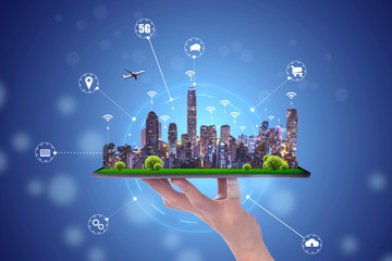 hand holding an empty digital tablet with Smart city with smart services and icons, internet of things, networks and augmented reality concept , night scape