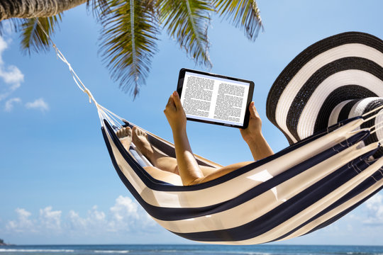 Woman In Hammock Reading The Book On Digital Tablet