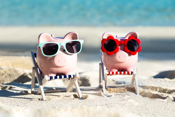 Two Pink Piggybanks With Sunglasses On Deck Chair At Beach Wall mural