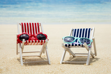 Two Type Of Sunglasses On Deck Chair At Beach