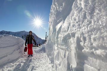 Senior man in ski gear walking through snow cleared pathway