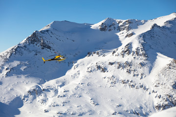 Rescue helicopter flying towards the mountains