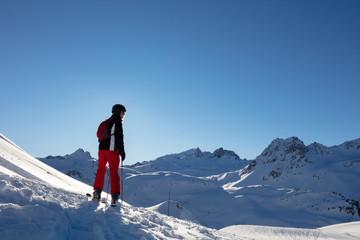 Senior man with ski poles on skis standing in snowy mountains