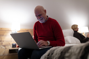 Senior man using laptop in hotel room and his wife reading