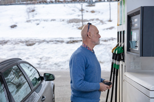 Senior man with wallet ready to pay at a gas station