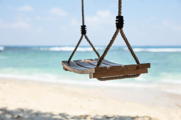An Empty Wooden Swing In Front Of Sea At Beach