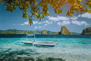 Island hopping trip El Nido. Incredible dreamlike exotic scenery with traditional filippino banca boat resting in turquoise water. tropical Palawan Island, Philippines