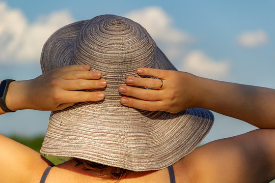 Summer time, vacation, pretty woman in an elegant hat, looking at the sky, enjoy summer and rest. Concept summer, vacation, holiday, day off