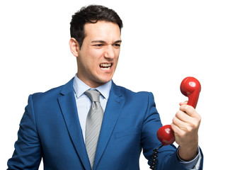 Angry businessman shouting on the phone isolated on white