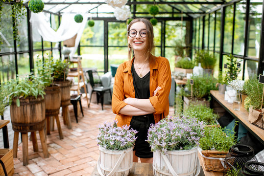 Portrait of a young and confident woman standing as business owner of the beautiful greenhouse or flower shop