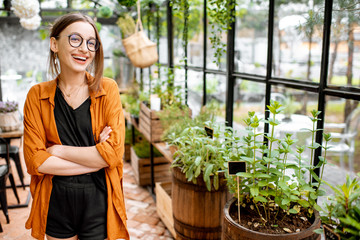 Portrait of a young and confident woman as a business owner of the beautiful greenhouse or flower shop