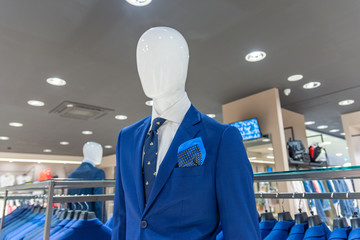 Close up of a mannequin in a fashion store in blue jacket, with a blue tie and scarf.