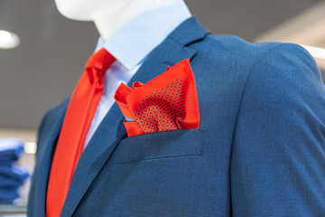 Close up of a mannequin in a fashion store in blue jacket, with a red tie and scarf.