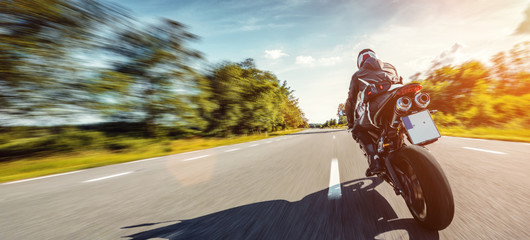motorbike on the road riding high speed. having fun riding the empty road on a motorcycle tour /...