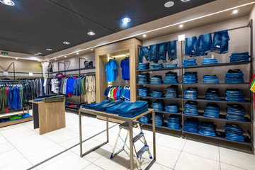 Internal view of a fashion store with generic jackets, mannequins, jeans and clothes.
