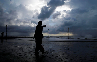 A woman takes photographs with her mobile phone against the backdrop of monsoon clouds at a beach in Kochi