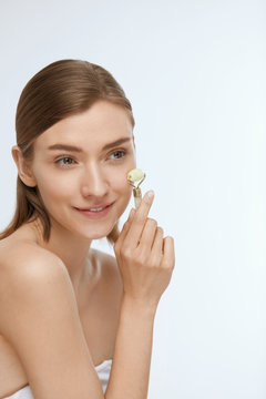 Face massage. Smiling woman using jade roller for skin care