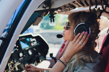 Female pilot in cockpit of helicopter before take off. Young woman helicopter pilot. Fototapete