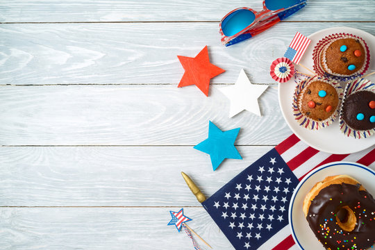 Happy Independence Day, 4th of July celebration concept with cupcakes, donuts and american flag on wooden background.