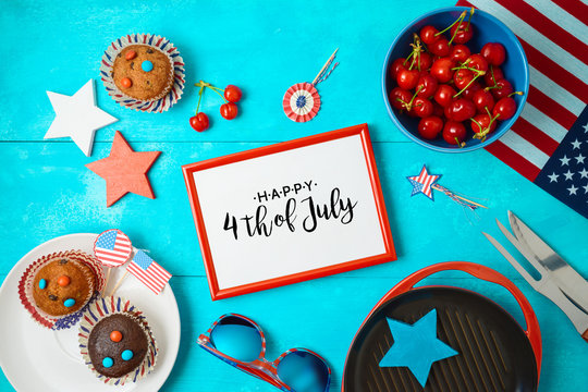Happy Independence Day, 4th of July celebration concept with frame, cupcakes and barbeque grill  on wooden background