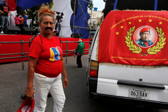 A woman wears a moustache to depict Venezuelan President Nicolas Maduro, next to a flag of late President Hugo Chavez, during a rally in support of the CLAP (Local Committees of Supply and Production) program in Caracas