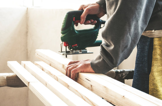 Craftsman cutting wooden plank with hacksaw