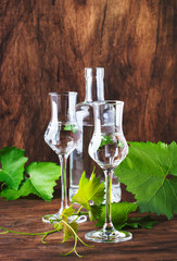 Grape vodka, pisco - traditional Peruvian strong alcoholic drink in elegant glasses on vintage wooden table, copy space