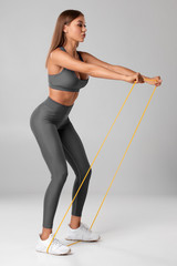 Fitness woman using a resistance band in her exercise routine. Sexy athletic girl workout with...