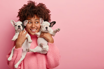 Image of delighted female hostess poses with two cute puppies, looks happily away, takes picture with pets, models over pink background, blank copy space, spend time together. Caring vet indoor
