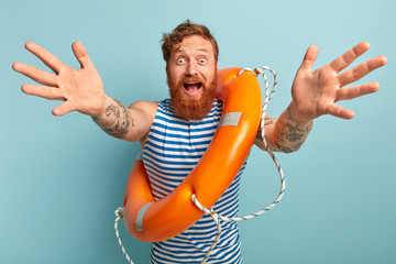 Handsome happy surprised man with orange lifebuoy indoor, wears striped blue and white vest, keeps hands outstretched, gives hug to someone, conducts lessons of safe swimming. Unexperienced swimmer