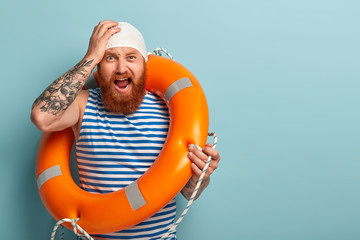 Frustrated professional male rescuer yells from despair, keeps hand on head, afraids of risk for drowning, uses special inflated life preserver, has tattoo on arm, stands over blue wall, blank space