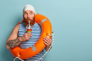 Summer time, lifestyle and recreation concept. Half length shot of bearded man poses with swimming circle and refreshing cold cocktail, wears special swimmingcap, isolated over blue background.