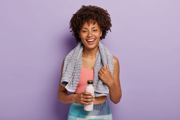Glad charming fitness woman drinks cold water, being thirsty after running, has towel on neck, wears top and leggings, stands against purple studio wall. People, cardio training and healthy lifestyle