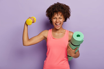 Funny happy dark skinned woman raises hand with dumbbell, shows biceps, holds rolled fitness mat, smiles broadly, wears pink casual vest, isolated over purple background. Fitness training at home
