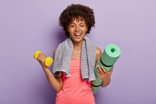 Happy Afro American woman lifts small weights, holds green karemat, ready for yoga exercises, smiles broadly, isolated over purple background, looks gladfully at camera. Workout with dumbbell