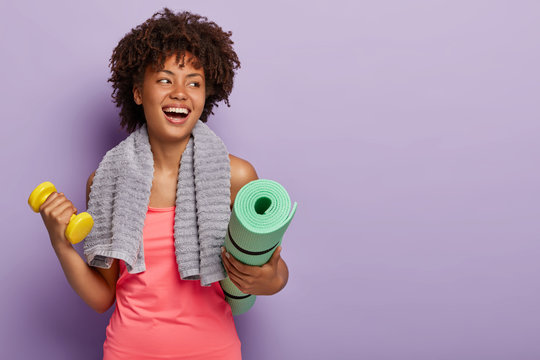 Positive dark skinned woman holds yoga mat and dumbbell, wears sportclothes, has towel on neck, looks aside with happy expression, exercises in gym, isolated over purple wall. Fitness and training