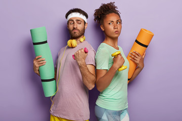Diverse sporty couple stand backs, hold dumbbells, fitness mats, has confident determined facial expressions, use sport equipment, listen music in headphones, stand over purple wall. Athletic family