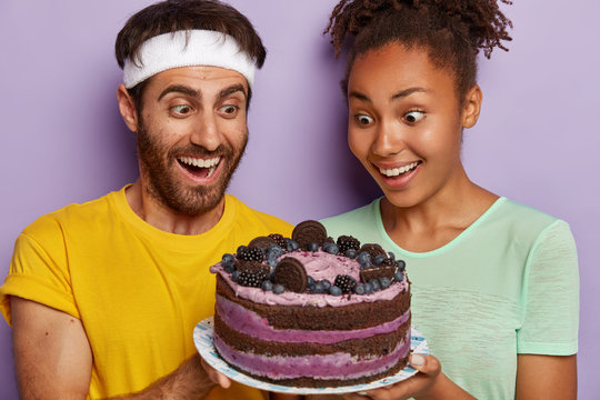 Headshot of happy female and male glad and surprised to get permission from fitness trainer to eat tasty cake, stare at dessert, feel temptation, have strong desire for eating pie. Proper nutrition