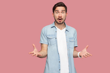 How you did this? Portrait of shocked sad bearded young man in blue casual style shirt standing with stressed face and looking at camera and asking. indoor studio shot, isolated on pink background.