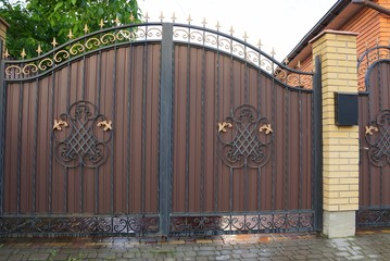 brown metal gate with a forged pattern and a brick fence on the sidewalk on the street