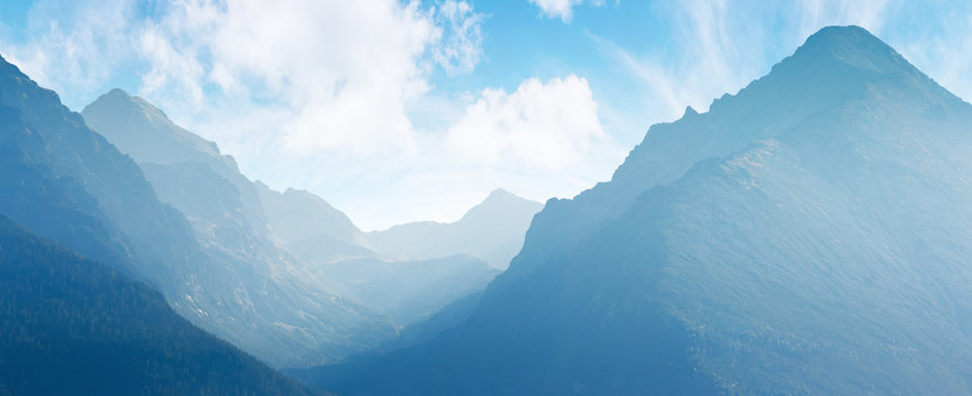 panorama of mountain ridge. bright scenery in afternoon hazy light. sky with fluffy clouds. valley between ridges. beautiful landscape backdrop