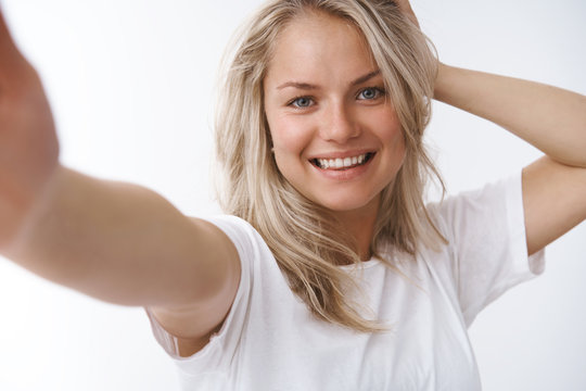 Woman taking selfie in morning on smartphone extending arm forward as holding camera holding arm behind head posing flirty and feminine smiling pleased with happy emotions over white background