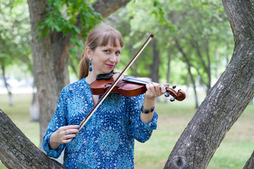The young Russian woman with a violin costs at a tree in the park in the summer