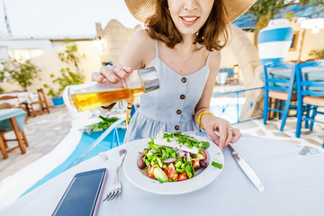 Young elegant girl in the restaurant seasoning salad with olive oil. Concept of Greek cuisine and fresh vegetables
