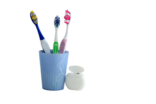 Three toothbrush in a cup and a floss for cleaning teeth on a white background. space for text and advertising.