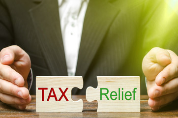 A businessman puts two puzzles with the words Tax and Relief. The concept of reducing the debt burden on business and local production to increase the competitiveness of their products. Economy