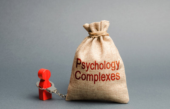 A person is handcuffed with a bag labeled psychological complexes. Feeling of inferiority and low self-esteem, low social skills, sociopathy and lack of communication. Phobias. Psychological help