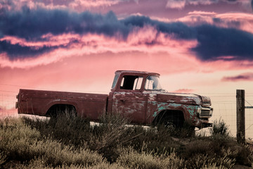 vintage pickup truck on a meadow at sunset